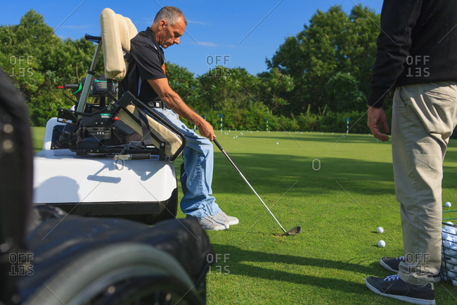 Man with a spinal cord injury in an adaptive cart at golf putting green with an instructor