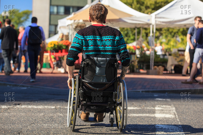 Trendy man with a spinal cord injury in wheelchair at a city outdoor market
