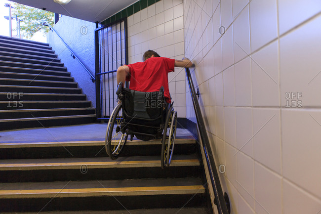 Trendy man with a spinal cord injury in wheelchair going down subway stairs backwards