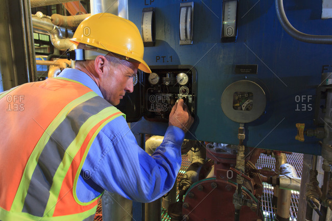 Engineer in electric power plant reviewing sensor readings