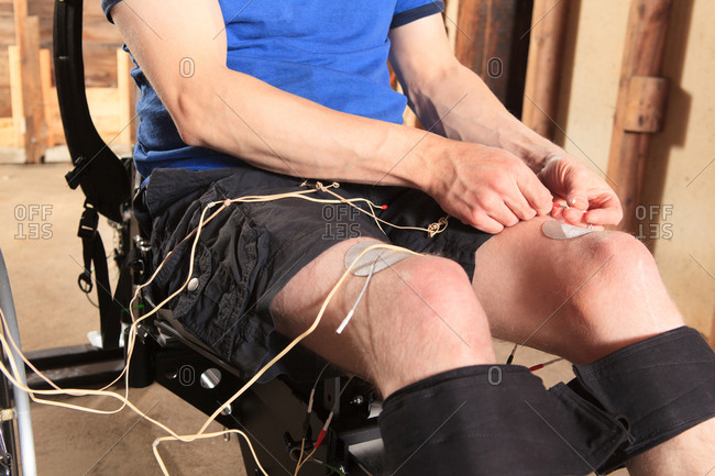 Man with spinal cord injury attaching wired patches to his knees for his muscle stimulator