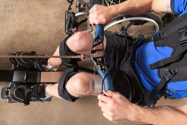 Man with spinal cord injury using his rowing machine with a muscle stimulator attached
