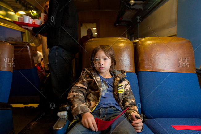 Boy in camouflage jacket riding on a train