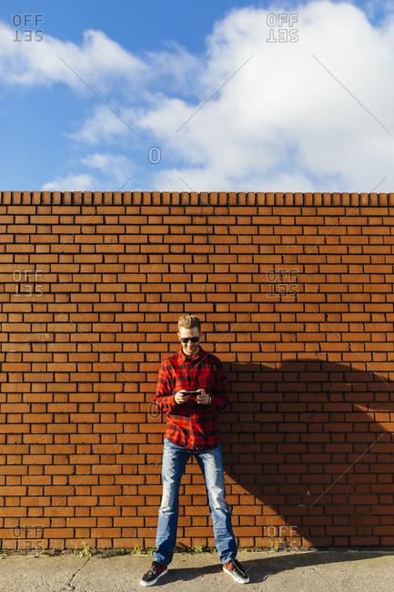 Young man at brick wall using a cell phone
