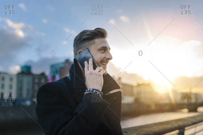 Smiling young businessman talking on the phone