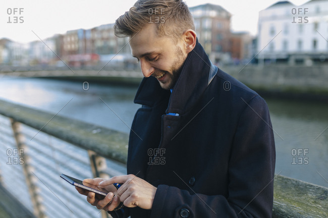 Smiling young businessman looking at his smartphone