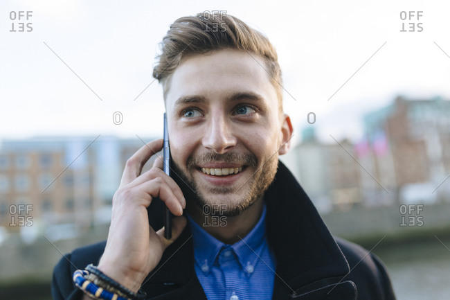 Portrait of smiling young businessman with a smartphone