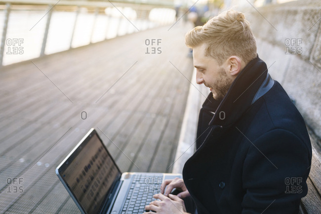 Young man sitting on a bench working with laptop