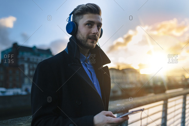 Young man listening to music with headphones at twilight