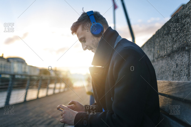 Young man sitting on a bench at backlight listening to music with headphones