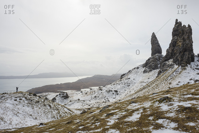 Boy taking a photo of the snow-covered Old Man of Storr