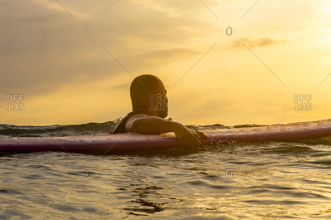 Surfer with surf board in the evening light
