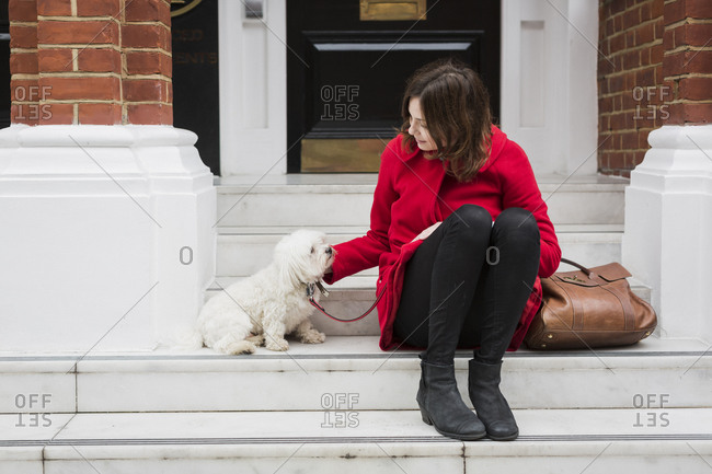 Young woman sitting on stairs besides her dog