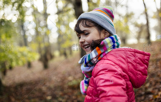 Happy little girl in the woods wearing cap and scarf in autumn