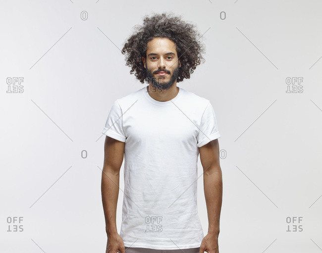 Portrait of bearded young man with curly brown hair wearing white t-shirt