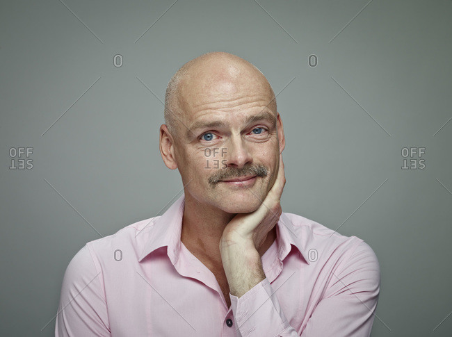 Portrait of bald man with moustache wearing pink shirt