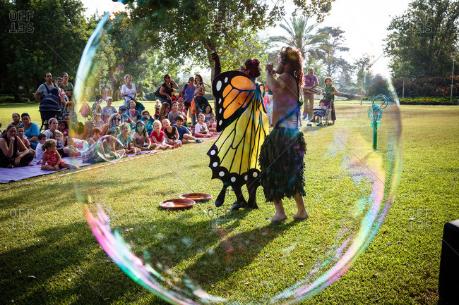 Zikhron Ya'akov, Israel - August 21, 2013: Large bubble in front of couple performing at Ramat Hanadiv Gardens