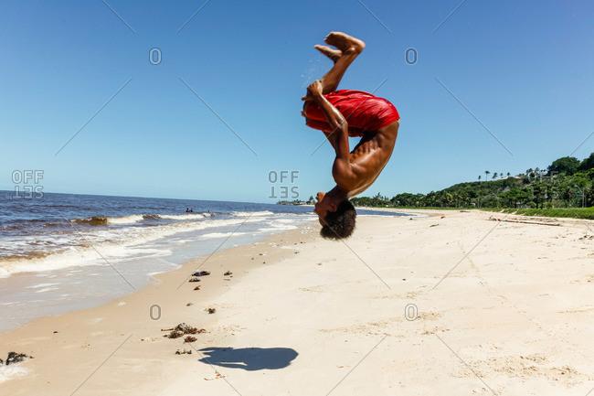 Young man doing a back flip on Rio da Vila beach, Porto Seguro, Bahia, Brazil