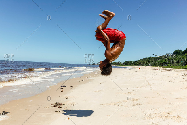 Young man doing a back flip on Rio da Vila beach, Porto Seguro, Bahia, Brazil