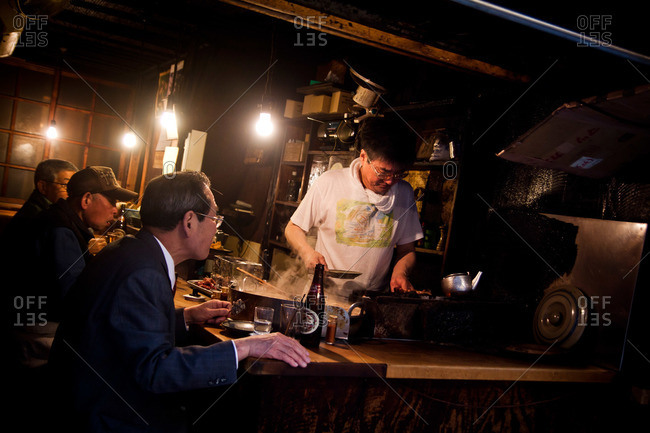 Shinjuku, Tokyo - April 20, 2011: Chef in a yakatori grill serving customers in Shinjuku, Tokyo