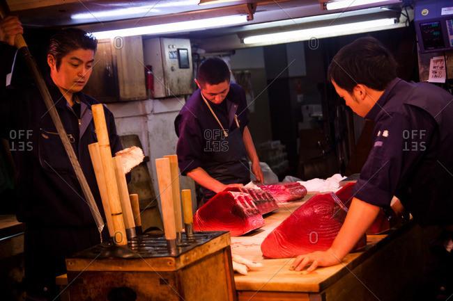 Tsukiji Fish Market - May 5, 2011: Three men cutting large fish at the Tsukiji Market
