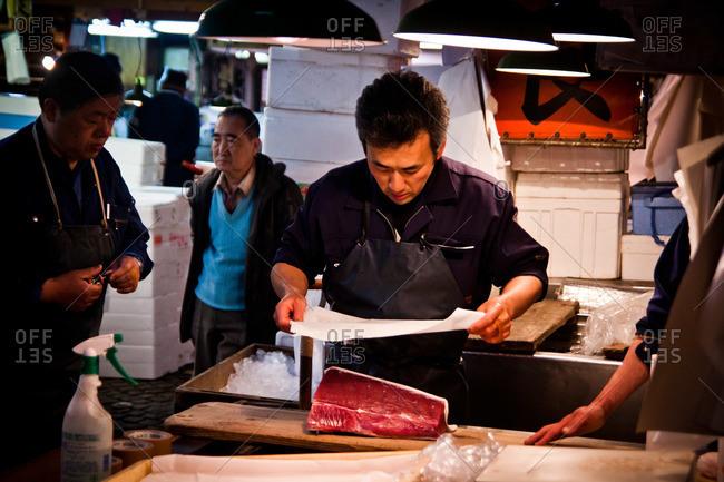 Tsukiji Fish Market - May 5, 2011: Man wrapping a fish in paper at the Tsukiji Market