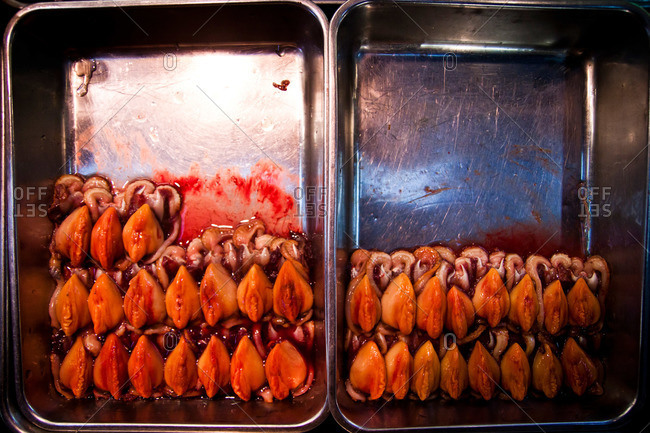 Trays half filled with seafood in an Asian fish market