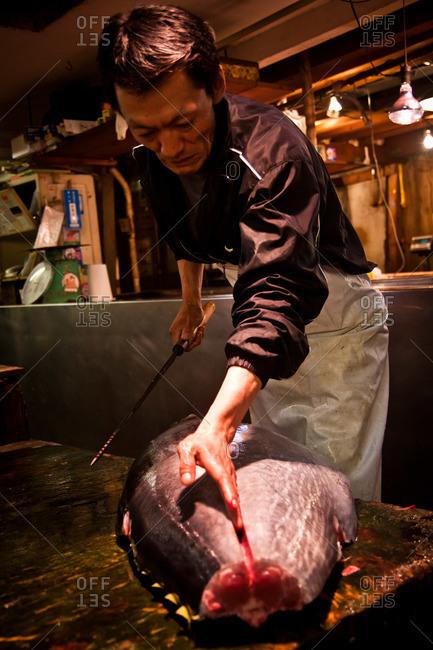 Tsukiji Fish Market - May 5, 2011: Fisherman gutting fish on a cutting board at the Tsukiji Market