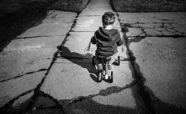 Little boy riding a training bicycle on a sidewalk