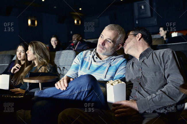 Man whispers in his partner's ear as they watch movie in theater