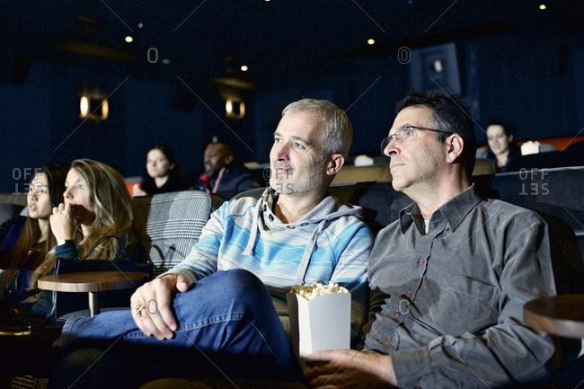 Two men enjoying movie together at cinema