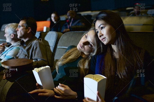 Woman resting her head on partner's shoulder in movie theater