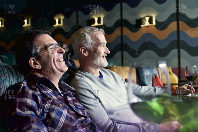 Men laughing together in movie theater