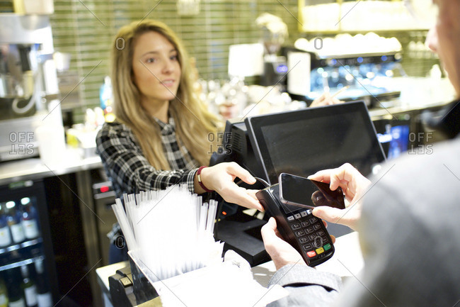 Cashier holding keypad to customer to scan with smartphone