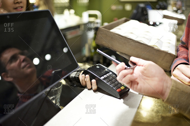 Man using smartphone to pay at concession stand