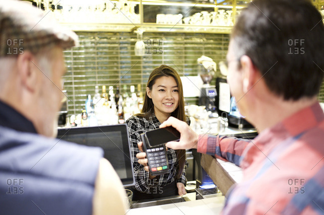 Customers using smartphone for payment at theater concession stand