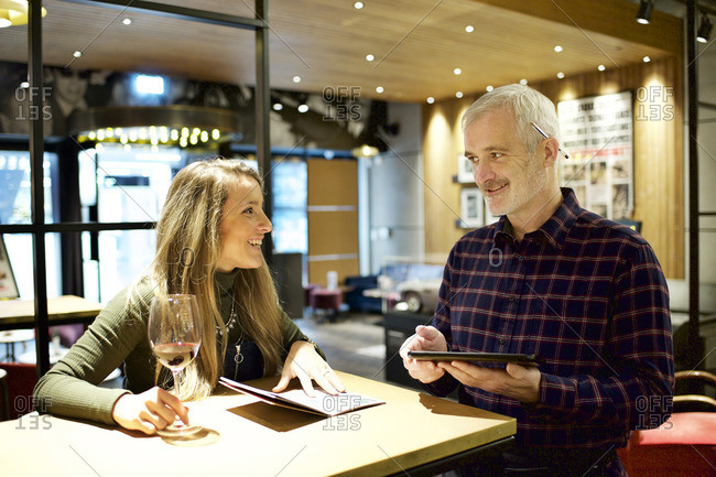 Waiter taking woman's order on a tablet computer