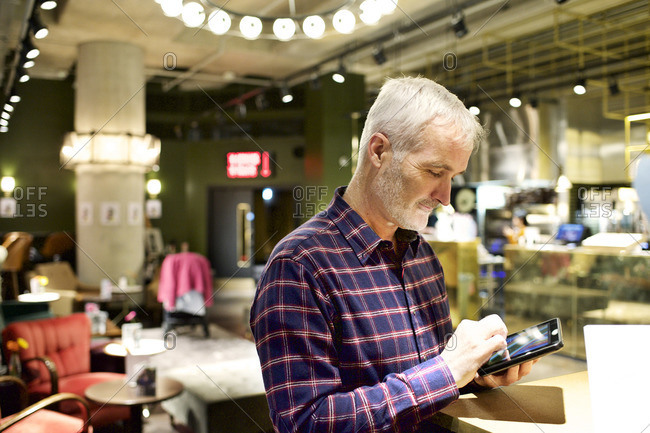 Man using tablet at cafe
