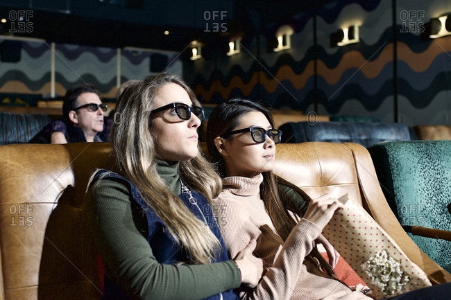 Women watch movie in 3D glasses