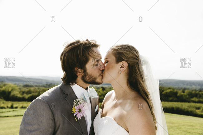 Bride and groom kissing in country