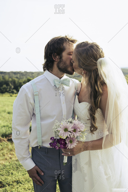 Bridal couple kissing each other outside
