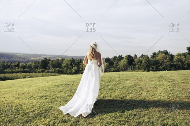 Bride in her dress on hilltop