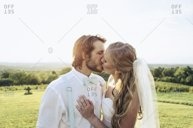 Bridal couple kissing in rural setting