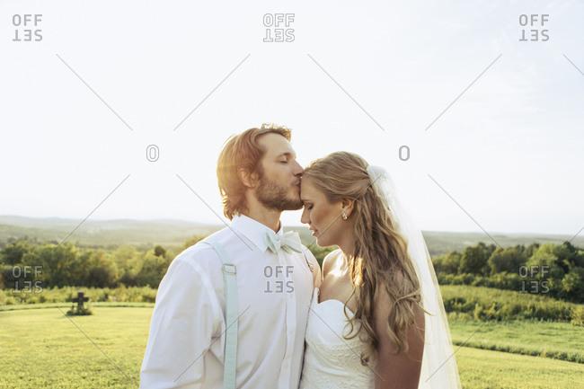 Groom kissing bride in rural setting