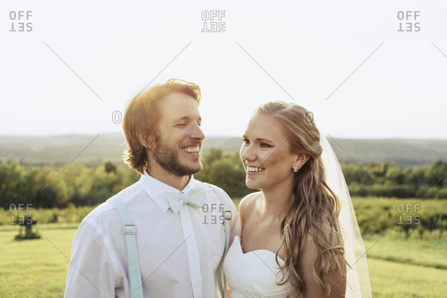 Smiling bridal couple together outside