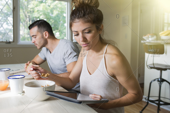 Woman with tablet at breakfast table
