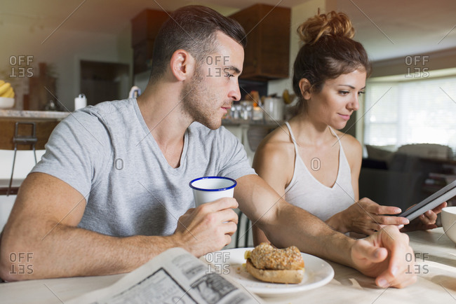 Couple reading tablet at breakfast table