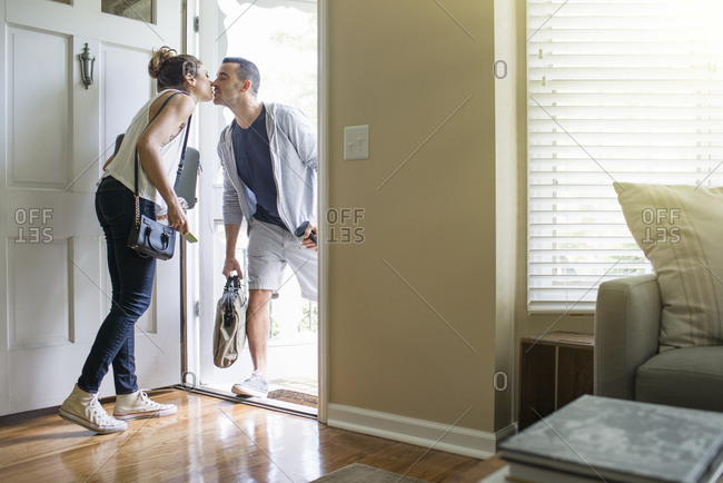 Couple kissing goodbye at front door