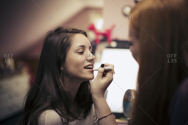 Woman putting lipstick on a friend