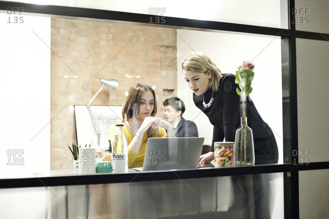 Young business women collaborating at a laptop
